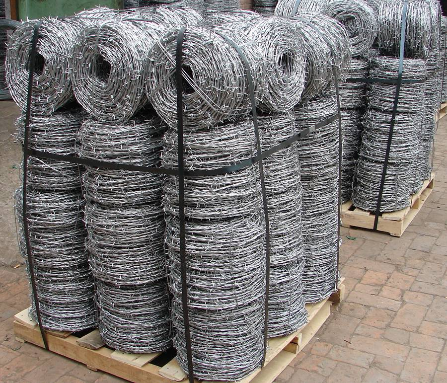 Many coils of galvanized barbed wire is packed with bailing strip on wooden pallet in workshop.