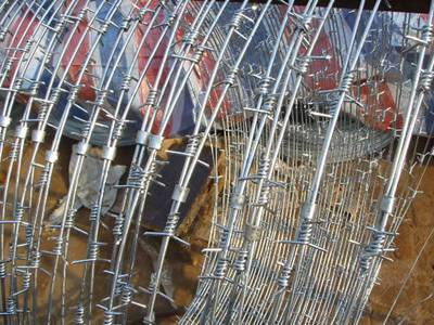 A stretching coil of concertina barbed wire with single twist type and clips.