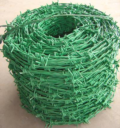 A big coil of PVC coated barbed wire with traditional twist type in green.
