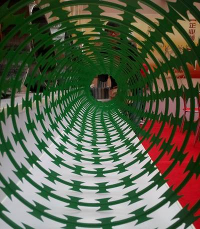 A stretching coil of PVC coated concertina razor wire in green.