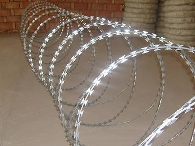 A roll of galvanized double spiral razor wire on the ground.
