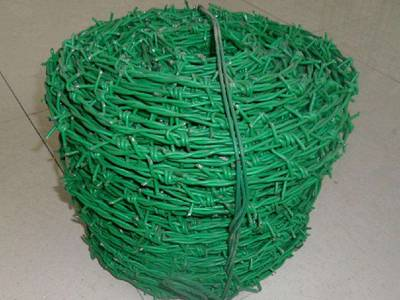 A roll of green color PVC coated barbed wire on the ground.