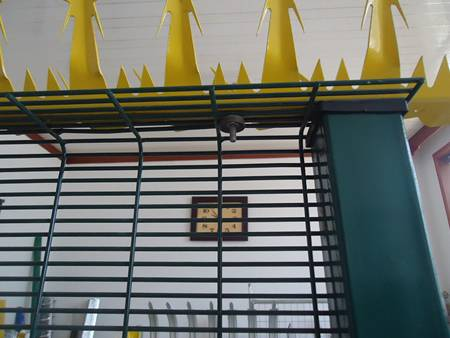 A row of wall spikes painted yellow color installed on green 358 mesh fence.