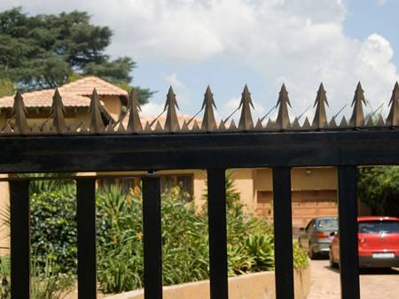 Some wall spikes on the gate of courtyard, and two cars parked in the courtyard.