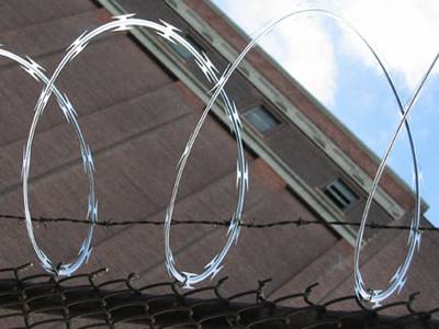 Concertina wire and barbed wire installed on chain link fence forming security fencing